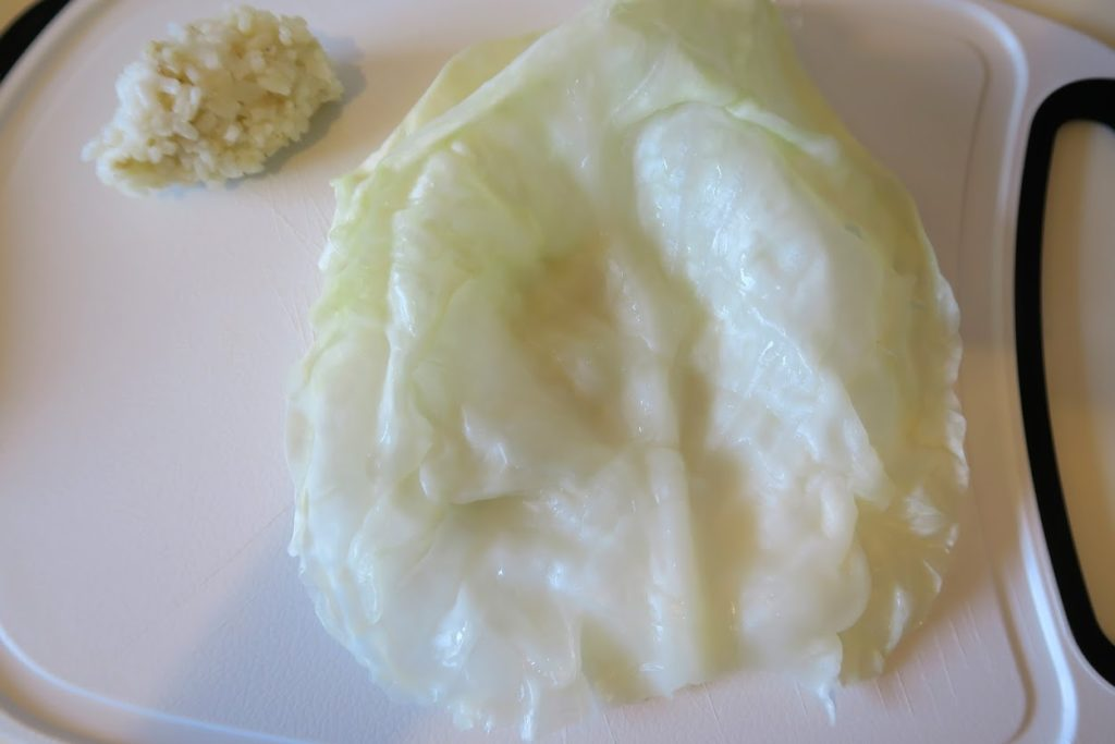 A whole cabbage leaf unfurled with a small ball of rice filling next to it