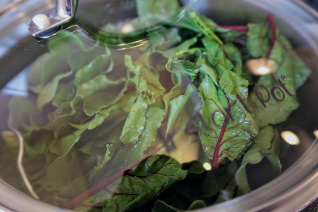 Beet leaves arranged vertically in the Instant Pot with the glass lid