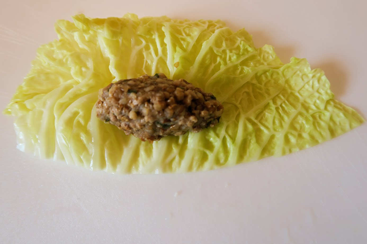 An oblong ball of filling sitting on half of a stemless cabbage leaf