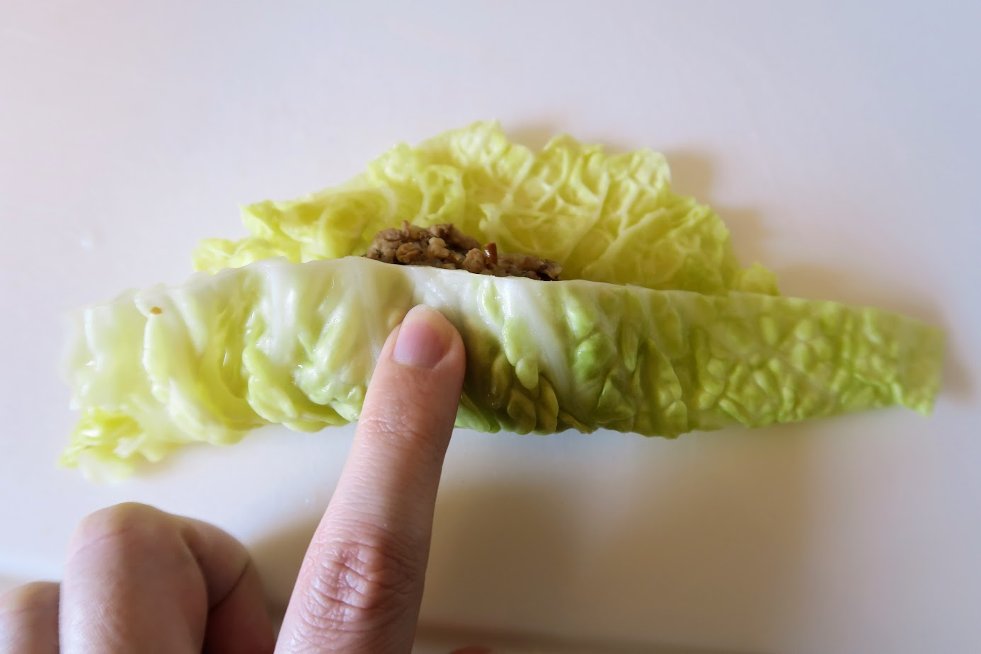 The bottom edge of the cabbage leaf partially covering the filling