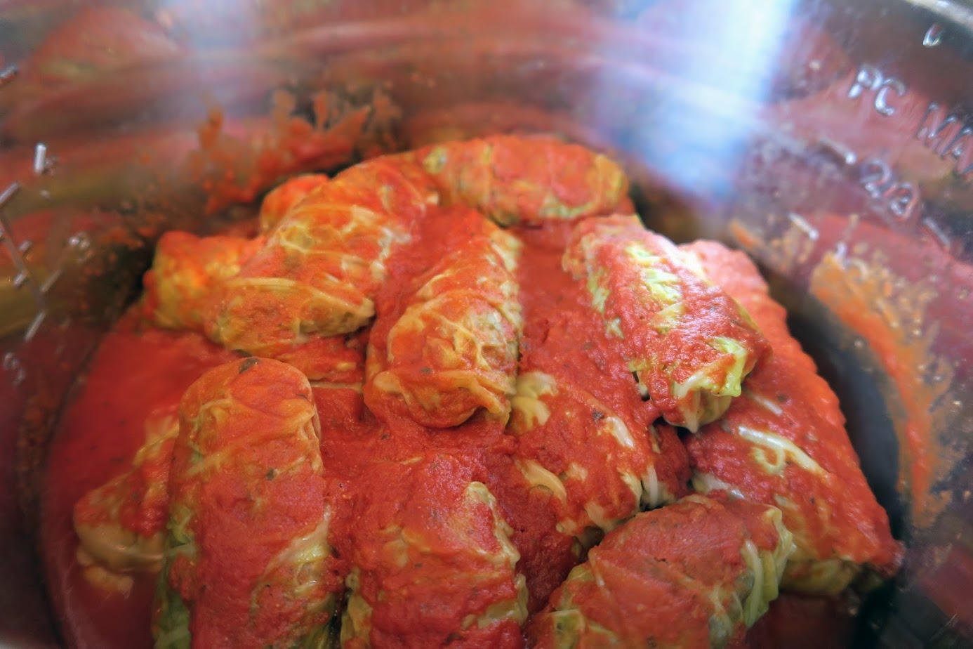Cooked cabbage rolls inside the Instant Pot covered in tomato sauce