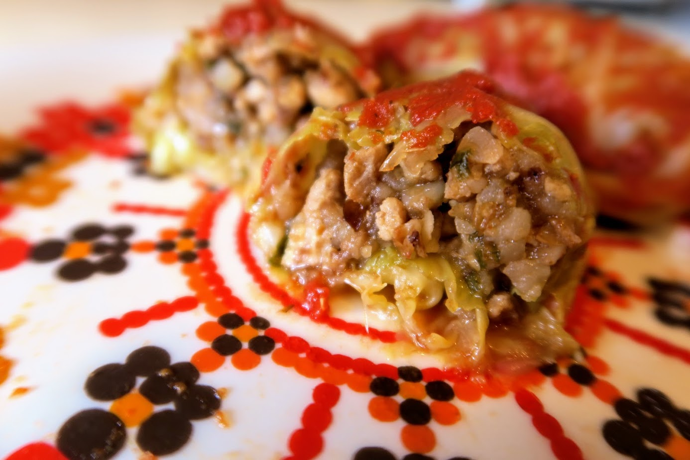 Three cabbage rolls on a plate with one cut into showing the buckwheat and meat filling