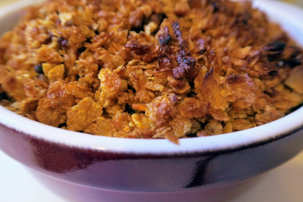 Baked casserole topped with crunchy corn flakes and butter