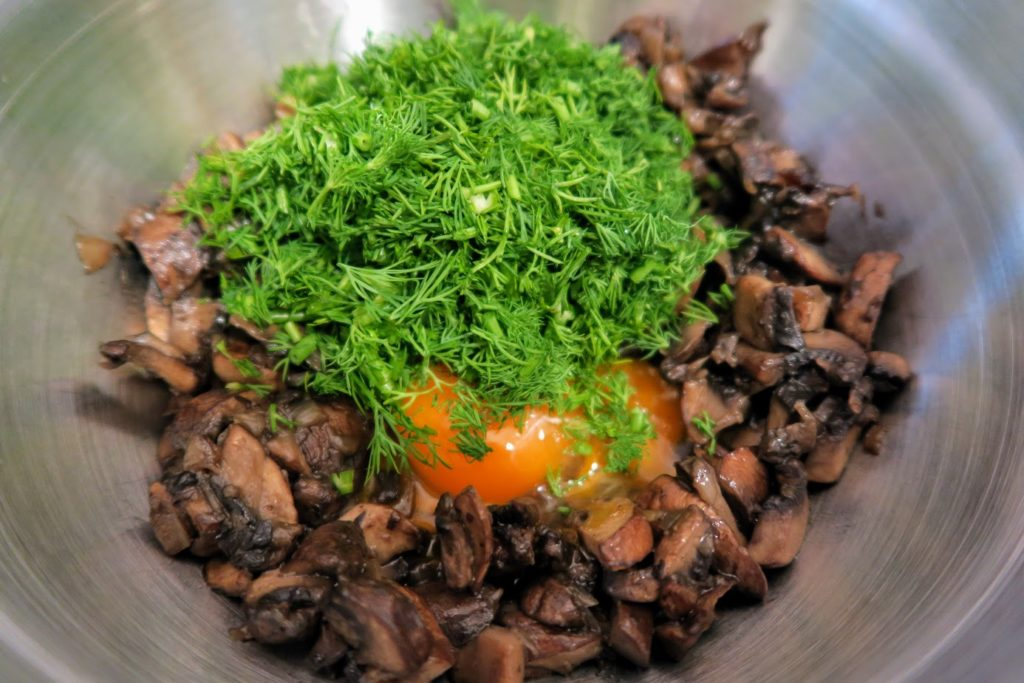 Cooked, chopped mushrooms with dill and 2 egg yolks in a bowl ready to be combined