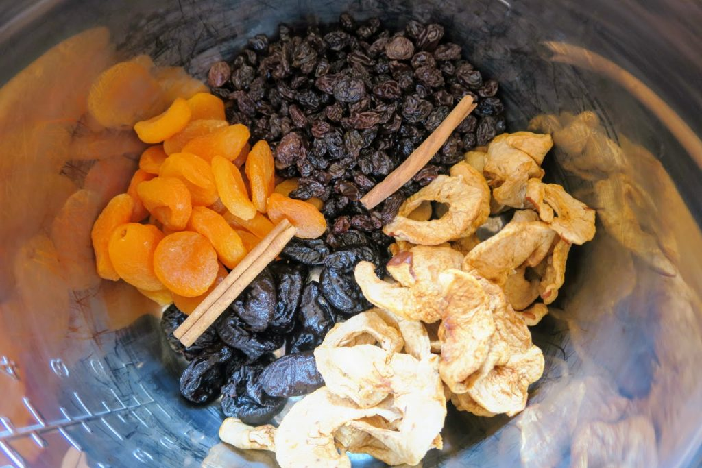 Dried apricots, dried apples, prunes and raisins arranged in the Instant Pot with cinnamon sticks