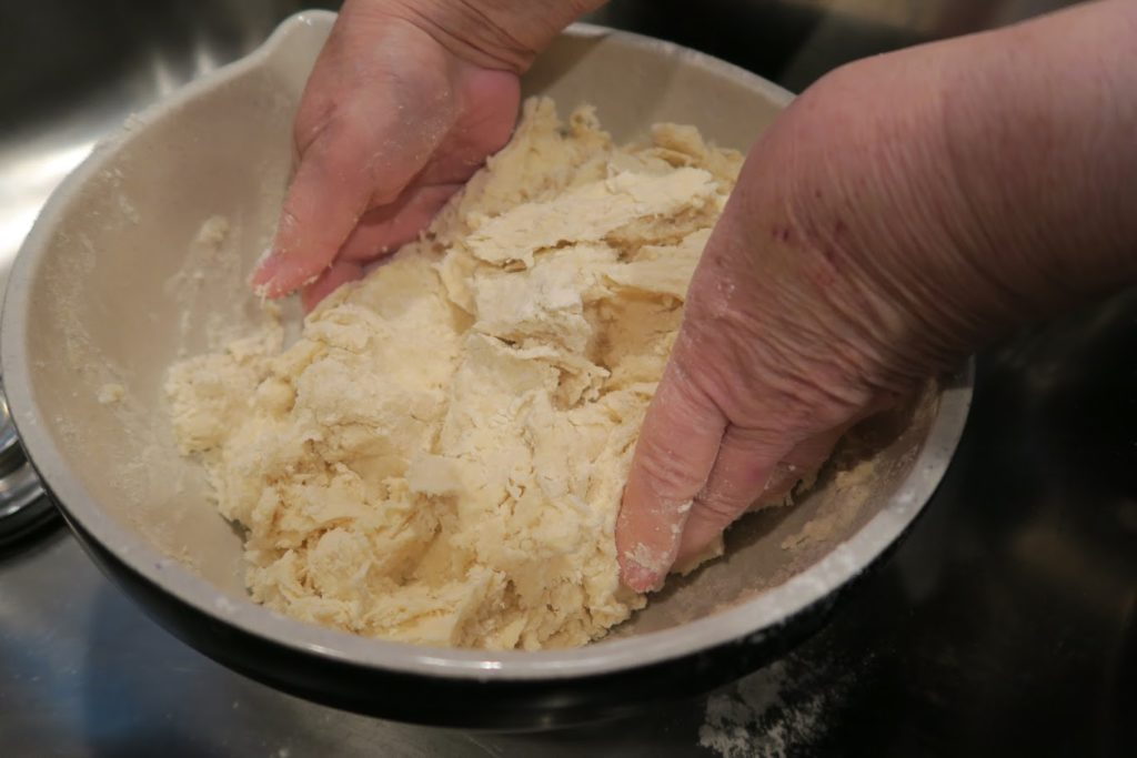 Hands kneading the dough inside a bowl
