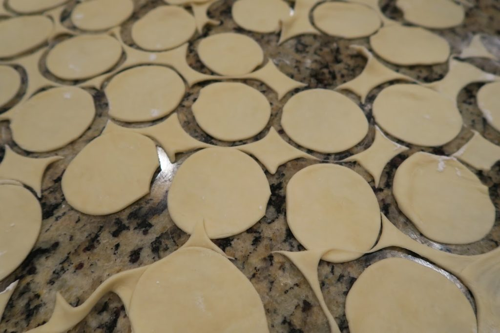 Circles cut out of the dough rolled out on a countertop