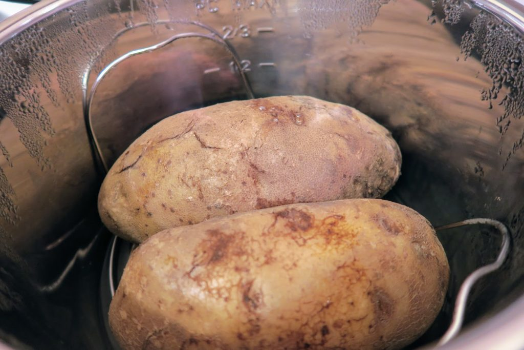 Two enormous Russet baking potatoes filling the Instant Pot on top of a wire rack