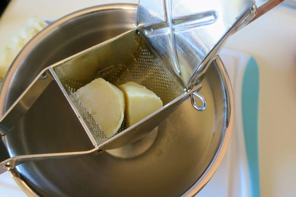 Peeled potatoes inside a potato ricer