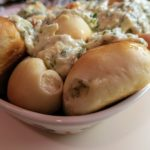 Baked pyrizhky in a casserole topped with dill cream sauce