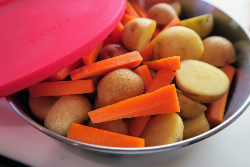 Halved new potatoes and carrot pieces in a pot-in-pot container