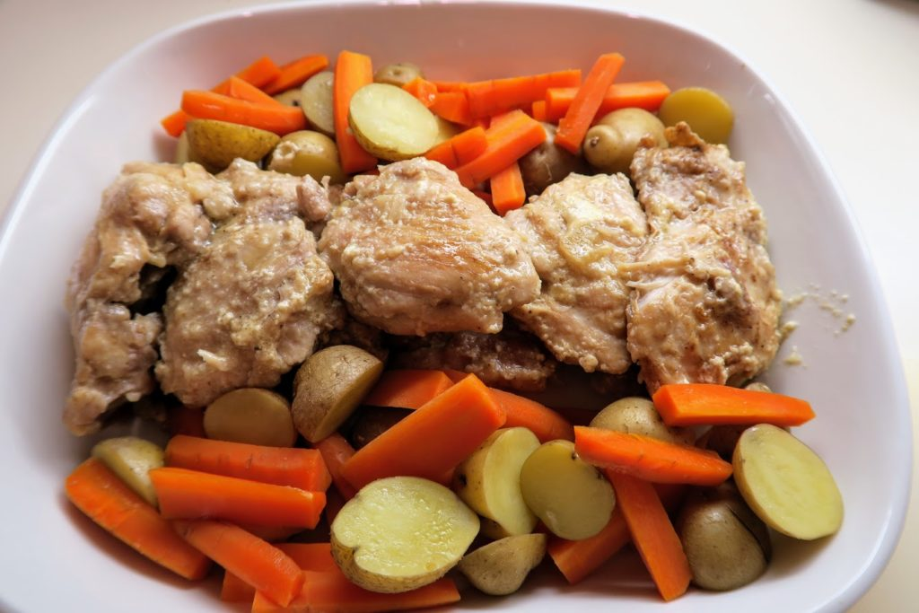 Cooked potatoes and carrots arranged on each side of the chicken