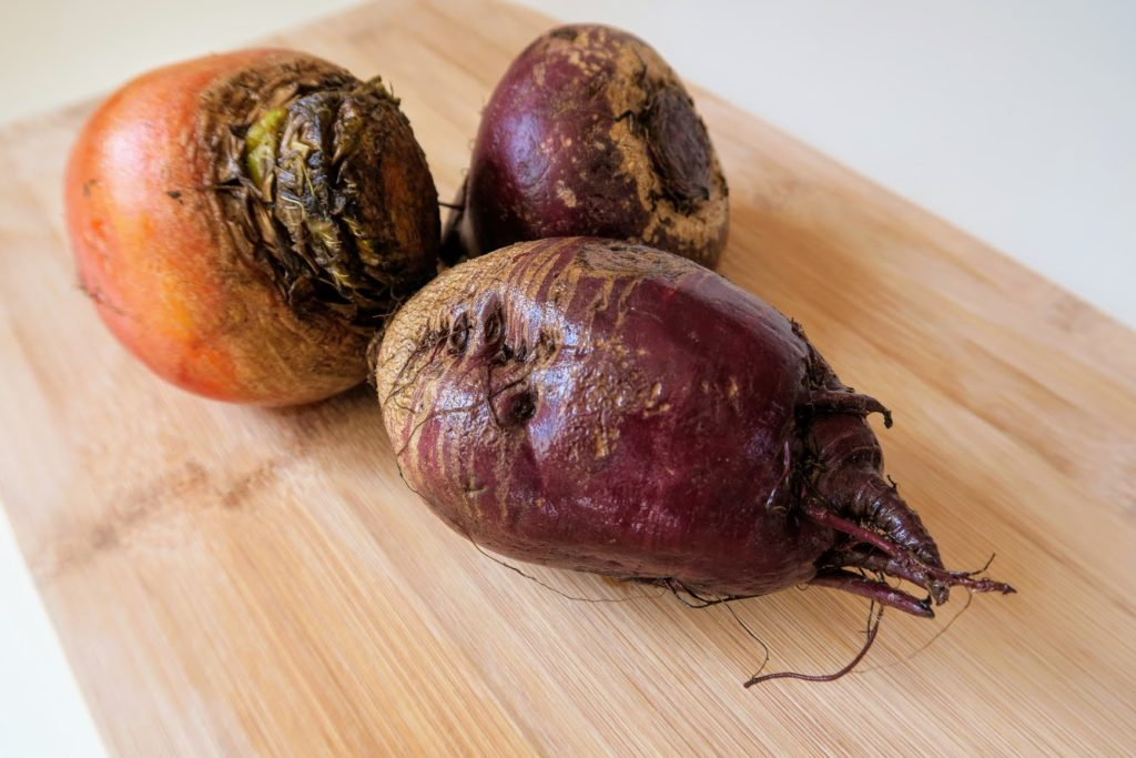 Two red beets and a golden beet rinsed off