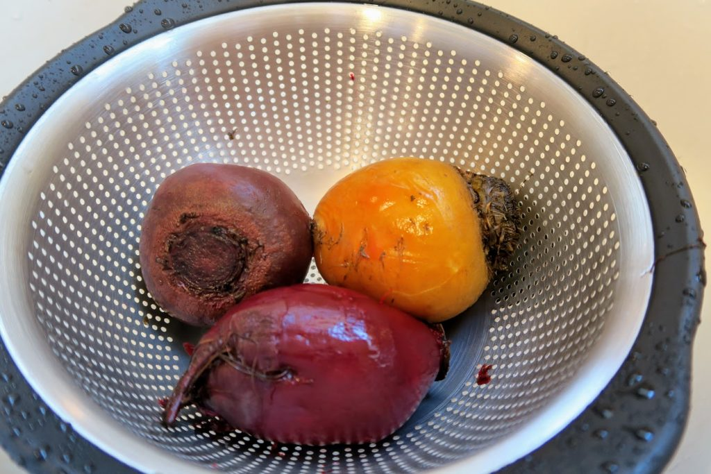 Three beets cooling off in a colander