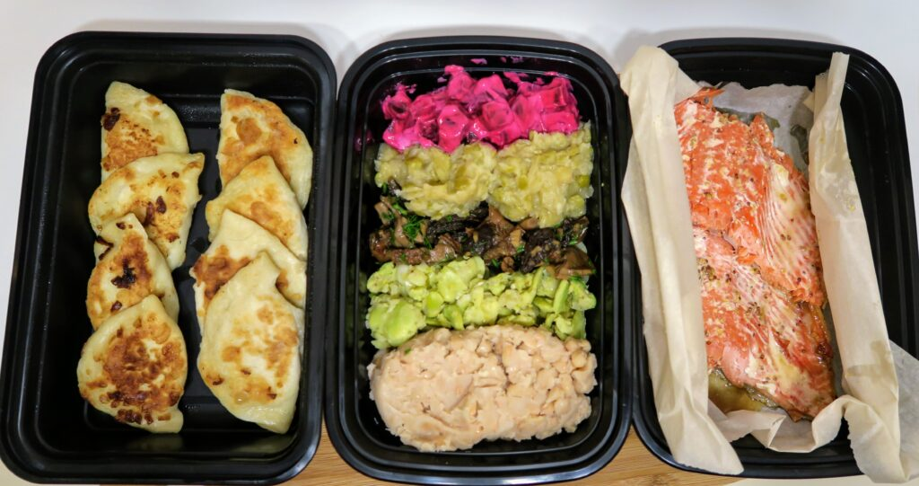 Sviata vecheria in 3 take-out containers with perohe, 5 vegetable/bean dishes and salmon